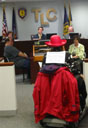 photo of far view of Jean Ryan speaking at a podium at TLC hearing
